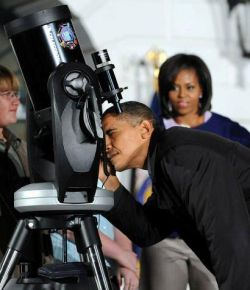 Obama pretending to look at stuff while TV crews shine bright lights on him.